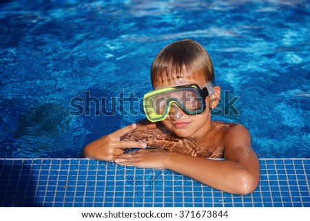 Portrait of a kid laughing in a swimming pool. - stock photo