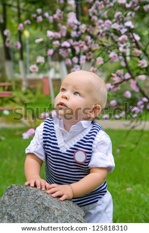 portrait of a kid looking up at something against a nature background - stock photo