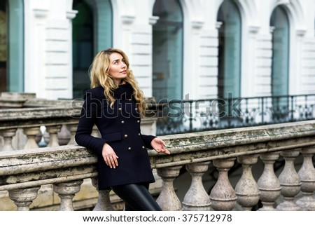 Portrait of a Lady with curled blonde hair in a classic coat in the city of Vienna. Expressive Blue eyes and happy smile - stock photo