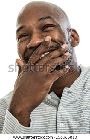 Portrait of a late 20s black man covering his mouth from laughter isolated on a white background
