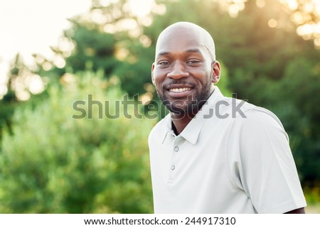 Portrait of a late 20s black man sitting at the park on a summer day with filtered effect - stock photo