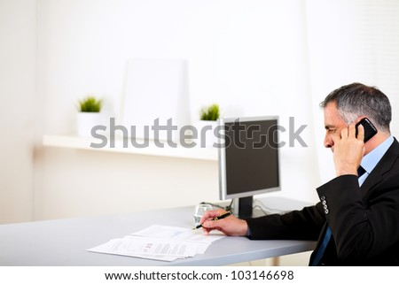 Portrait of a latin executive talking on cellphone at the office - stock photo