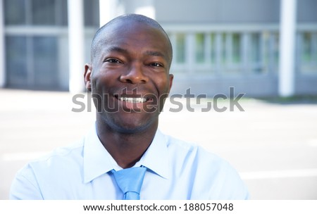 Portrait of a laughing african businessman in front of his office - stock photo