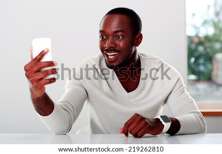 Portrait of a laughing african man looking on smartphone - stock photo