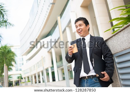 Portrait of a laughing businessman outdoors - stock photo