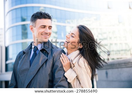 Portrait of a laughing couple flirting outdoors with glass building on background - stock photo