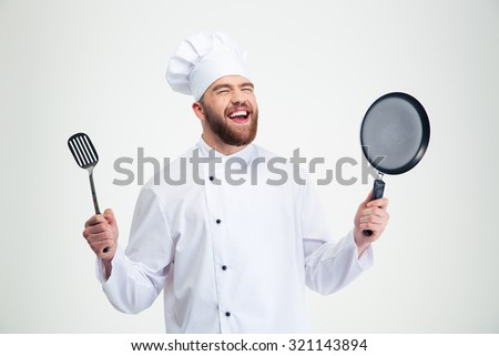 Portrait of a laughing male chef cook holding spoon and pan isolated on a white background - stock photo