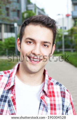 Portrait of a laughing student with checked shirt - stock photo
