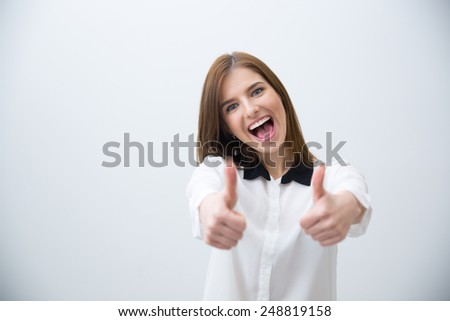 Portrait of a laughing woman with thumb up over gray background - stock photo