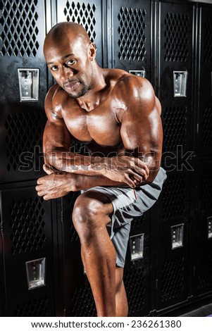 Portrait of a lean toned and fit muscular man under dramatic low key lighting. - stock photo