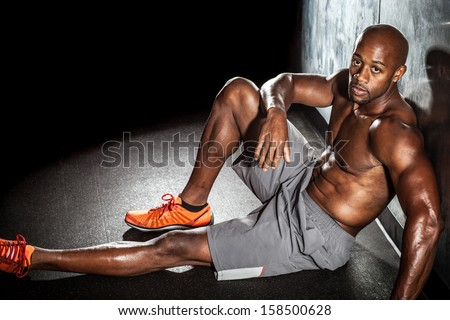 Portrait of a lean toned and ripped muscle fitness man under dramatic low key lighting and copy space. - stock photo