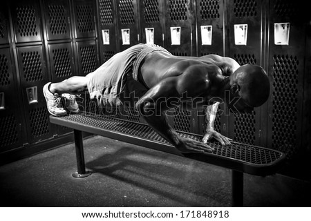 Portrait of a lean toned and ripped muscle fitness man under dramatic low key lighting in black and white. - stock photo