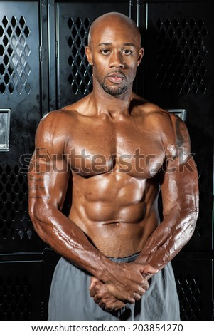 Portrait of a lean toned and ripped muscle fitness man under dramatic low key lighting in the locker room. - stock photo