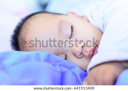 Portrait of a little adorable infant baby sleeping on the bed.