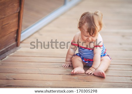 portrait of a little adorable infant girl sitting on the floor in summer park outdoors