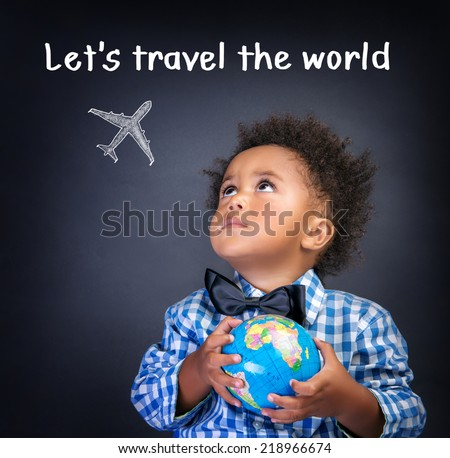 Portrait of a little African American schoolboy holding in hands small globe, dreaming about traveling all over the world, happy childhood concept - stock photo