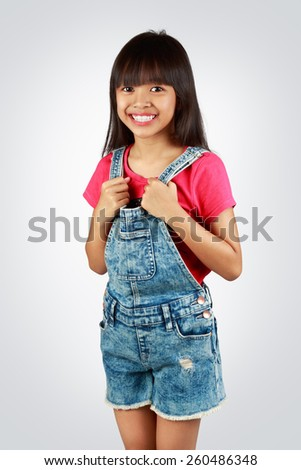 Portrait of a little asian girl standing, Isolated on grey background - stock photo