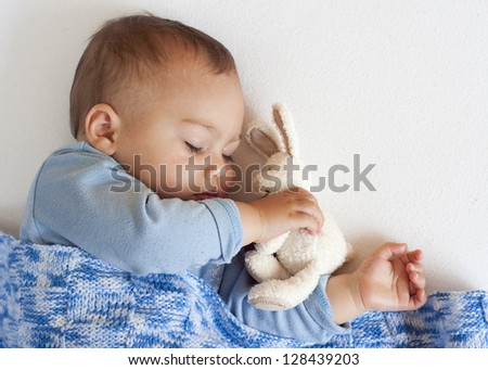 Portrait of a little baby boy sleeping under a blue blanket holding a white soft toy rabbit.