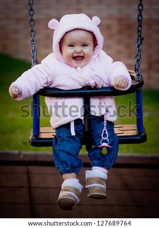 portrait of a little baby in a swing - stock photo