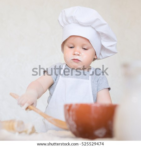 POrtrait of a little baby scullion is kneading dough in an apron and chef's hat isolated on blue background. Cooking child lifestyle concept