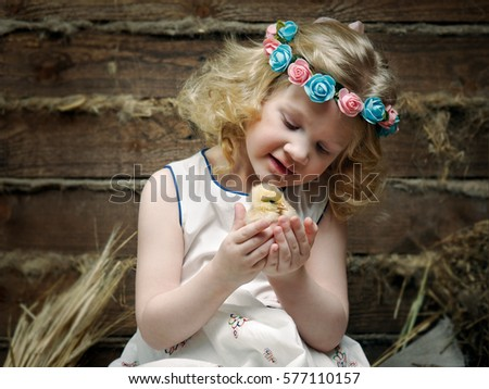 Portrait of a little beautiful girl with a newborn chick