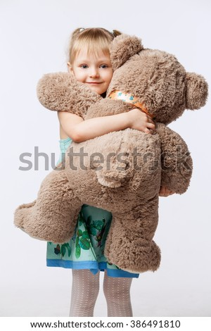 Portrait of a little blonde girl hugging a teddy bear toy, isolated on white background - stock photo
