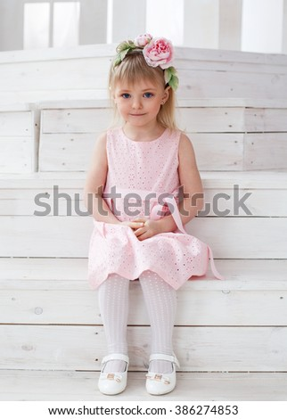 Portrait of a little blonde girl in a flower wreath sitting on the stairs