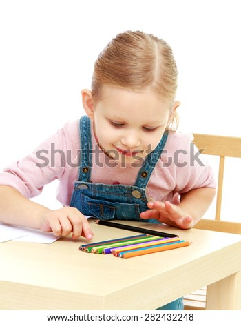 Portrait of a little blonde who is sitting at the table and chooses a colored pencil- isolated on white background