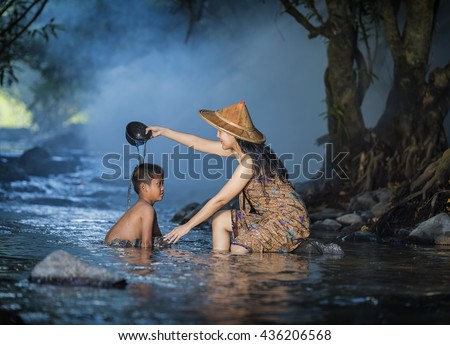 Portrait ,of a little boy and his mother in a stream . - stock photo