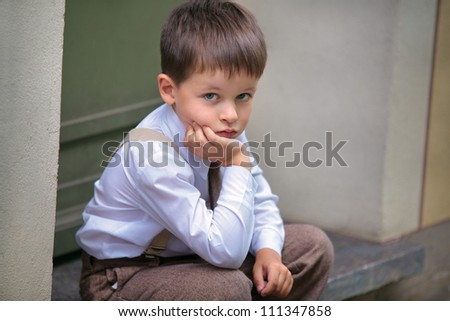 Portrait of a little boy having relax on the porch - stock photo