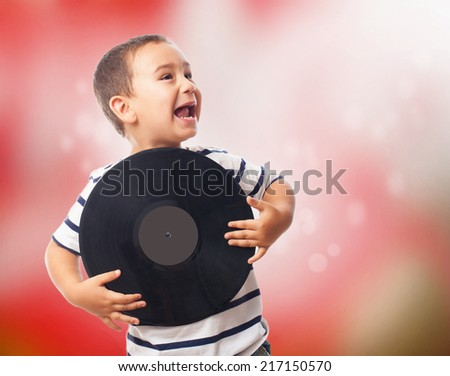 portrait of a little boy holding a vinyl record