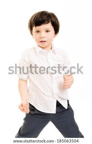 Portrait of a little boy in a white shirt in a fighting pose against a white background