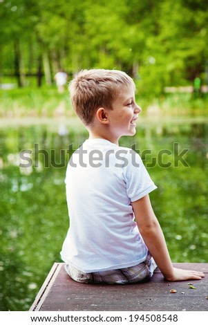 portrait of a little boy in the forest and lake - stock photo