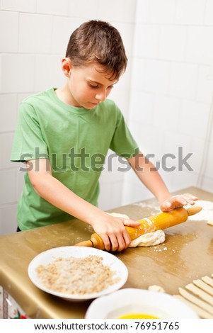 Portrait of a little boy in the kitchen using rolling pin to prepare the dough for cookies - stock photo