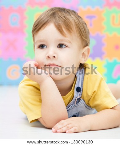 Portrait of a little boy laying on floor - stock photo
