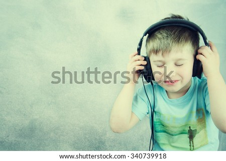Portrait of a little boy listening to music on headphones - stock photo
