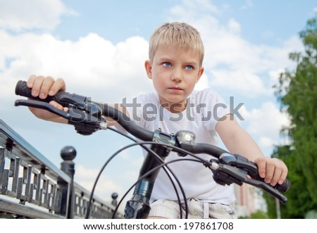 portrait of a little boy on bicycle - stock photo