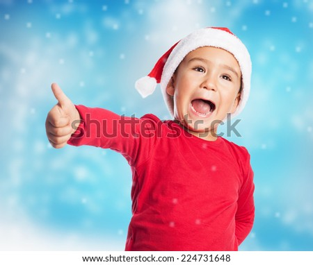 portrait of a little boy on christmas time with thumb up - stock photo