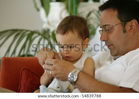 Portrait of a little boy playing a phone sitting on a man - stock photo