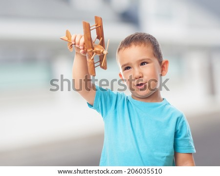 portrait of a little boy playing with a plane