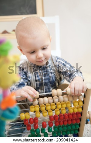 portrait of a little boy playing with abacus