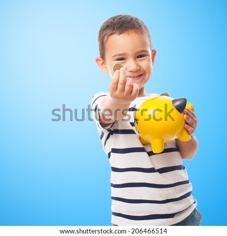portrait of a little boy putting money on a moneybox - stock photo