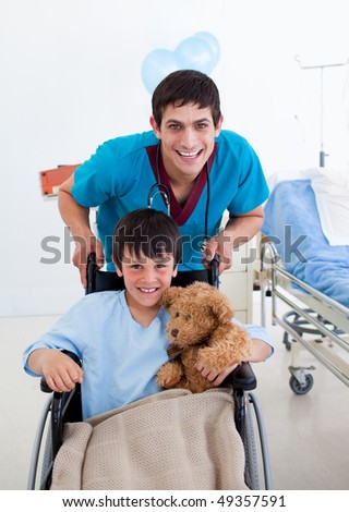 Portrait of a little boy sitting on wheelchair and a doctor at the hospital - stock photo