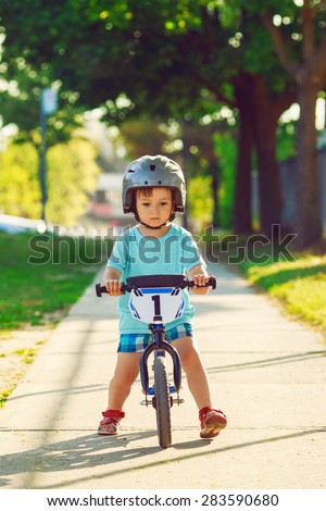 Portrait of a little boy toddler riding a balance bike in helmet on the road outside outdoors on a bright sunny spring summer day, seasonal child activity concept, healthy lifestyle - stock photo