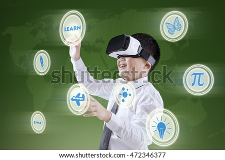 Portrait of a little boy using a virtual screen while wearing virtual reality headset