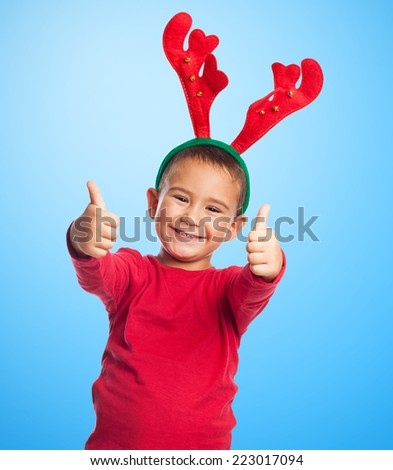 portrait of a little boy wearing a reindeer headband and doing the okay gesture - stock photo