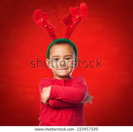 portrait of a little boy wearing a reindeer headband and standing with crossed arms - stock photo