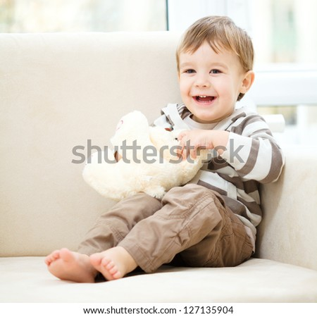 Portrait of a little boy with his teddy bear, indoor shoot - stock photo
