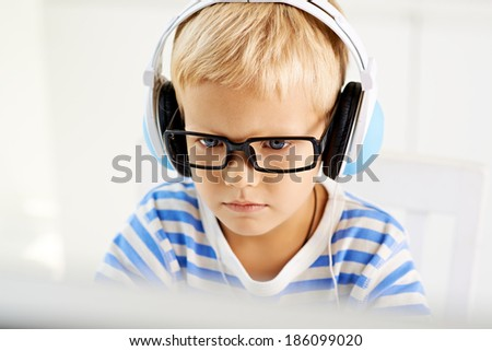 Portrait of a little concentrated boy in headphones - stock photo