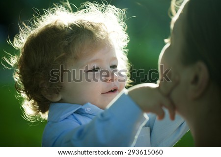 Portrait of a little curly baby boy explores and touching mom's face carefully with love outdoor closeup, horizontal photo - stock photo